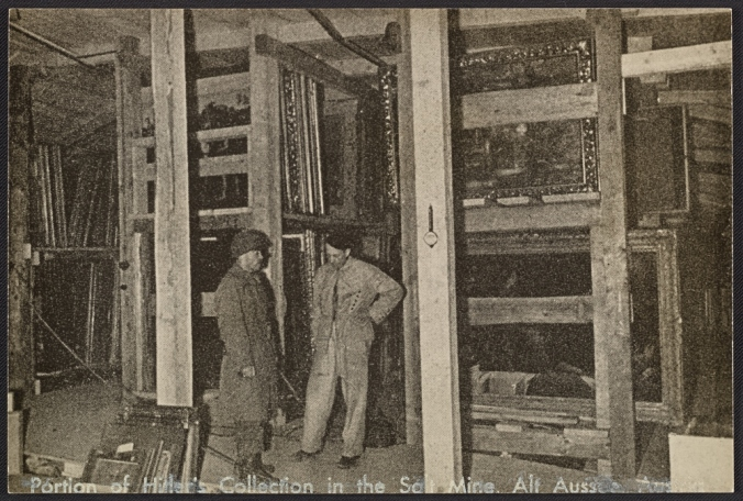 Two men standing by racks of paintings inside a salt mine in Altaussee, Austria, circa 1945 / unidentified photographer. Andrew Carnduff Ritchie papers, Archives of American Art, Smithsonian Institution.